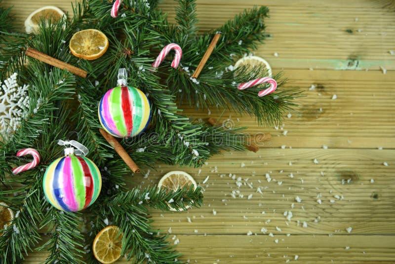 A imagem da fotografia do Natal com ramo de árvore verde deixa a canela fatias alaranjadas e decorações e neve coloridas da quinq foto de stock