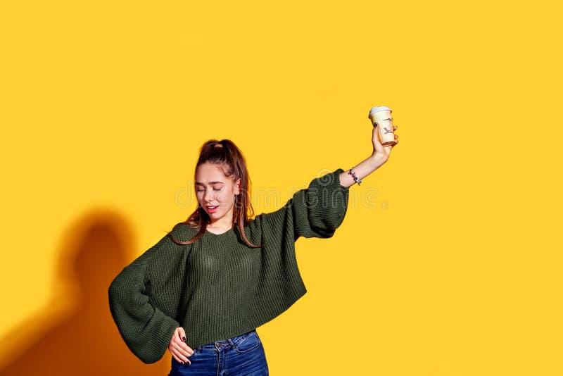 Imagem da jovem mulher bonita que sorri e que guarda o café afastado no copo de papel sobre o fundo amarelo fotos de stock
