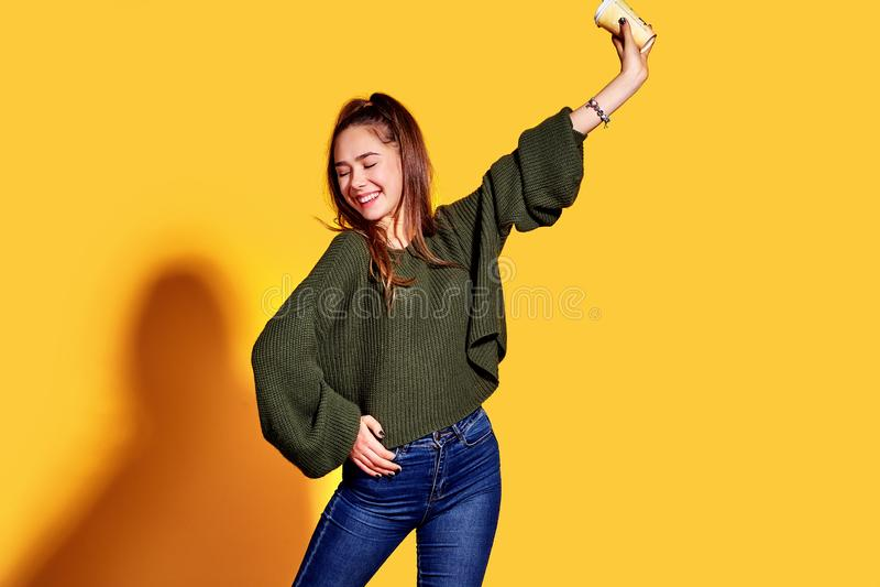 Imagem da jovem mulher bonita que sorri e que guarda o café afastado no copo de papel sobre o fundo amarelo foto de stock
