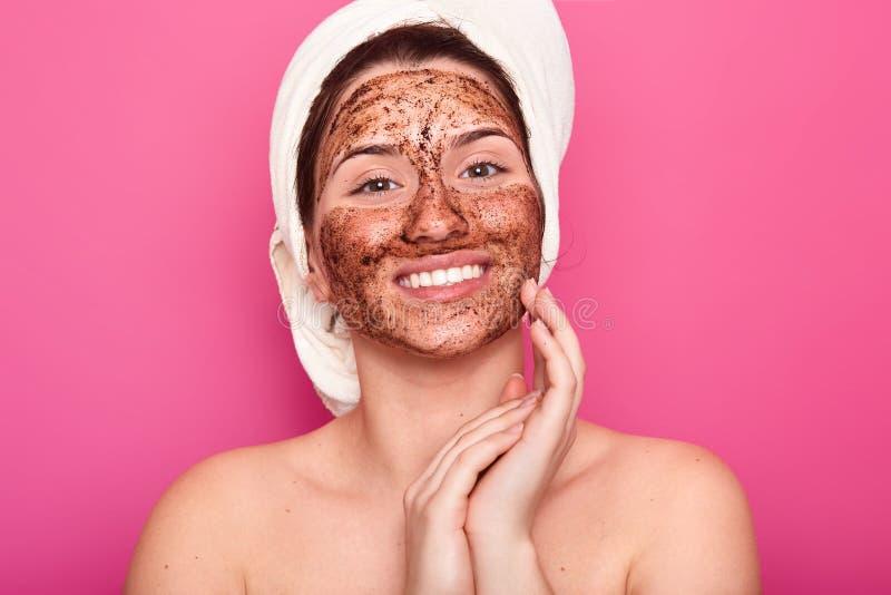 A imagem da jovem mulher com a toalha branca em sua cabeça, tem o corpo despido, levanta smilling sobre a parede cor-de-rosa, ma fotos de stock