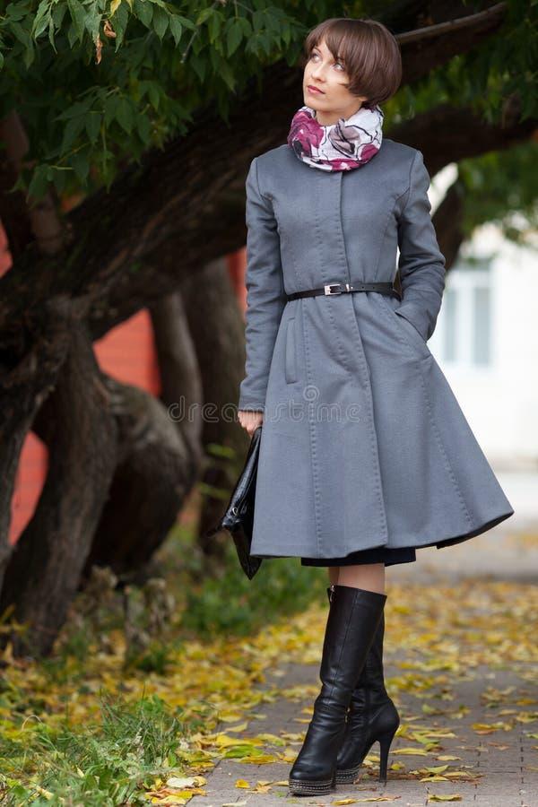 Imagem da jovem mulher de sorriso no revestimento cinzento que anda no parque fotografia de stock royalty free