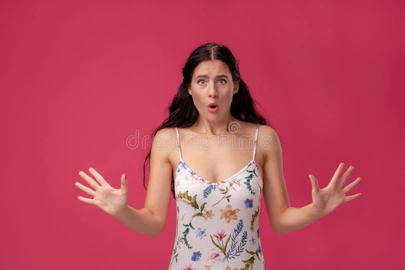 Imagem da jovem mulher gritando entusiasmado no fundo coral imagem de stock royalty free