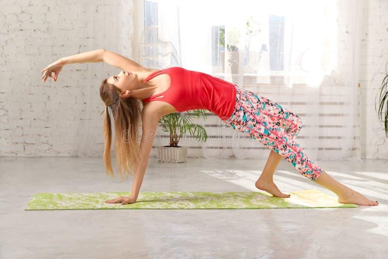 Imagem da jovem mulher loura bonita desportiva no sportswear que dá certo no salão, fazendo a variação da pose da ponte imagem de stock royalty free
