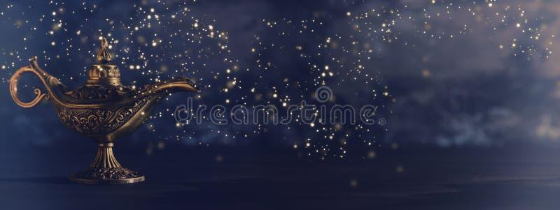 A imagem da lâmpada de aladdin misteriosa mágica com brilho de incandescência ilumina-se sobre o fundo preto Lâmpada dos desejos fotos de stock royalty free