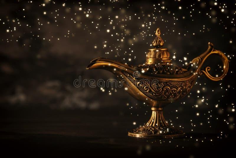 A imagem da lâmpada de aladdin misteriosa mágica com brilho de incandescência ilumina-se sobre o fundo preto Lâmpada dos desejos fotos de stock