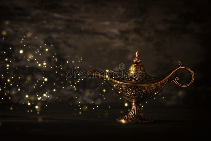 A imagem da lâmpada de aladdin misteriosa mágica com faísca do brilho ilumina-se sobre o fundo preto Lâmpada dos desejos fotografia de stock