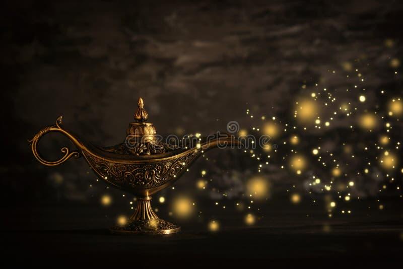 A imagem da lâmpada de aladdin misteriosa mágica com faísca do brilho ilumina-se sobre o fundo preto Lâmpada dos desejos fotos de stock royalty free