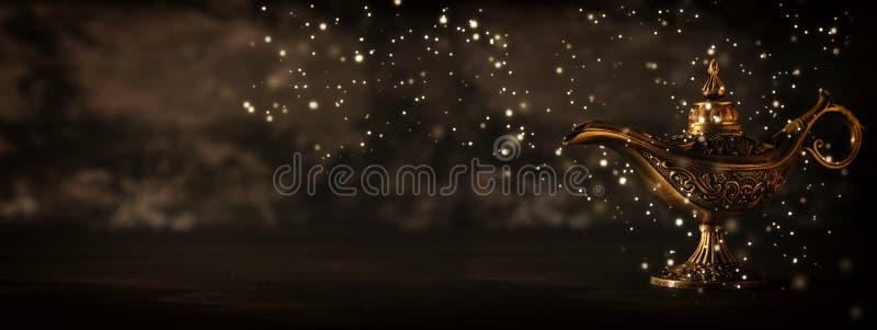 A imagem da lâmpada de aladdin misteriosa mágica com faísca do brilho ilumina-se sobre o fundo preto Lâmpada dos desejos imagens de stock royalty free