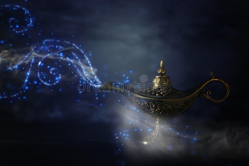 Imagem da lâmpada de aladdin misteriosa mágica com fumo da faísca do brilho sobre o fundo preto Lâmpada dos desejos imagem de stock