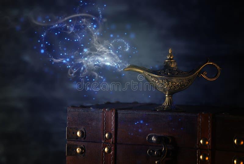 Imagem da lâmpada de aladdin misteriosa mágica com fumo da faísca do brilho sobre o fundo preto Lâmpada dos desejos foto de stock royalty free