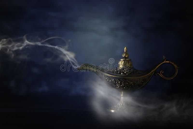 Imagem da lâmpada de aladdin misteriosa mágica com fumo sobre o fundo preto Lâmpada dos desejos imagens de stock royalty free
