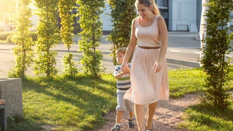 Imagem da mãe nova feliz com 3 anos jogo e corredor pequenos velhos de filho no campo de jogos das crianças no parque fotografia de stock royalty free