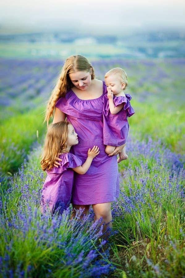 Imagem da mãe nova que abraça duas crianças pequenas, retrato do close up da família feliz, fêmea moreno bonito com dois imagem de stock