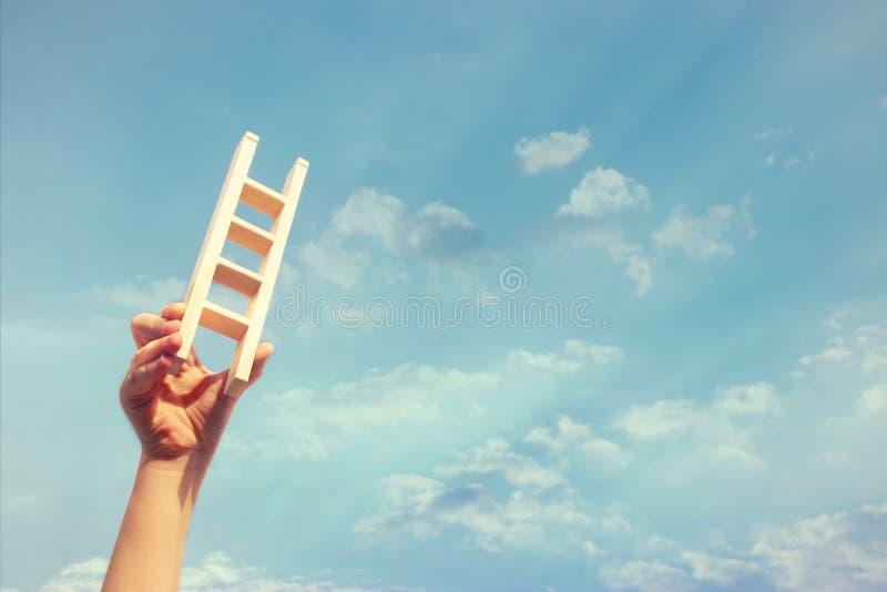 Imagem da mão da criança que mantém uma escada contra o céu Educação e conceito do sucesso fotografia de stock
