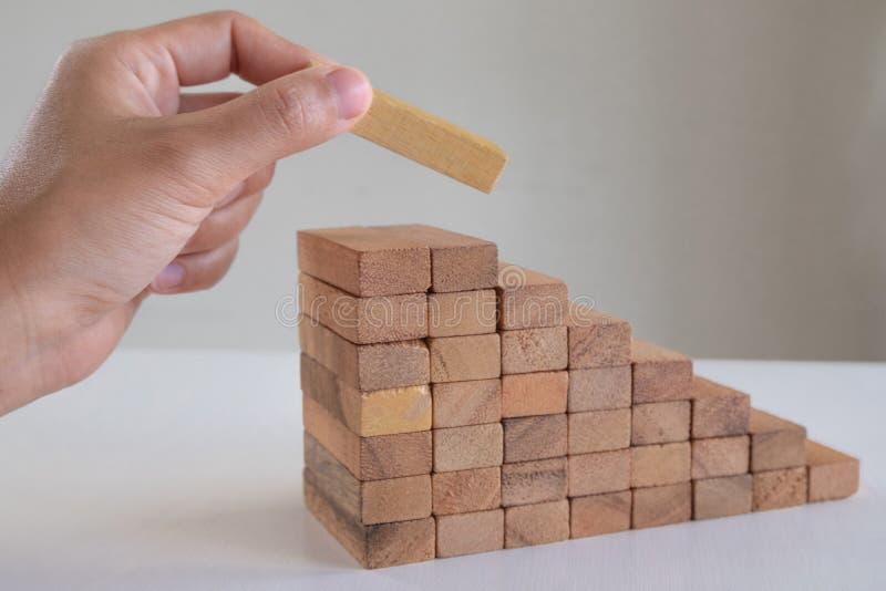 Imagem da mão que guarda o jogo de madeira dos blocos ao crescimento acima do negócio Risco de plano da gestão e da estratégia foto de stock