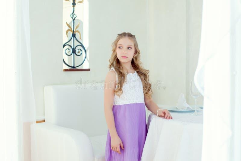 Imagem da menina bonito séria que levanta na tabela foto de stock