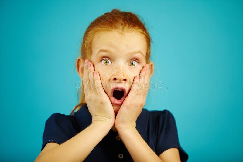 A imagem da menina chocado põe suas mãos a seu mordente, aberto sua boca, expressa a confusão e o desespero, tem sincero fotografia de stock