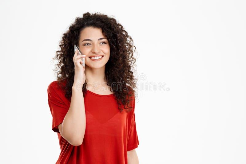 Imagem da menina encaracolado alegre que fala em seu telefone imagens de stock
