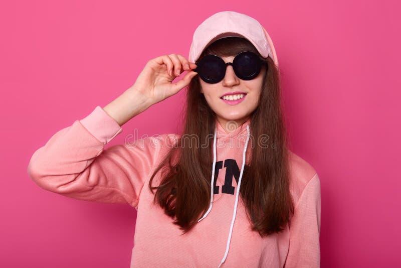 A imagem da menina fresca moreno veste o hoodie e o tamp?o cor-de-rosa Os suportes da jovem senhora isolados sobre o fundo cor-de imagem de stock