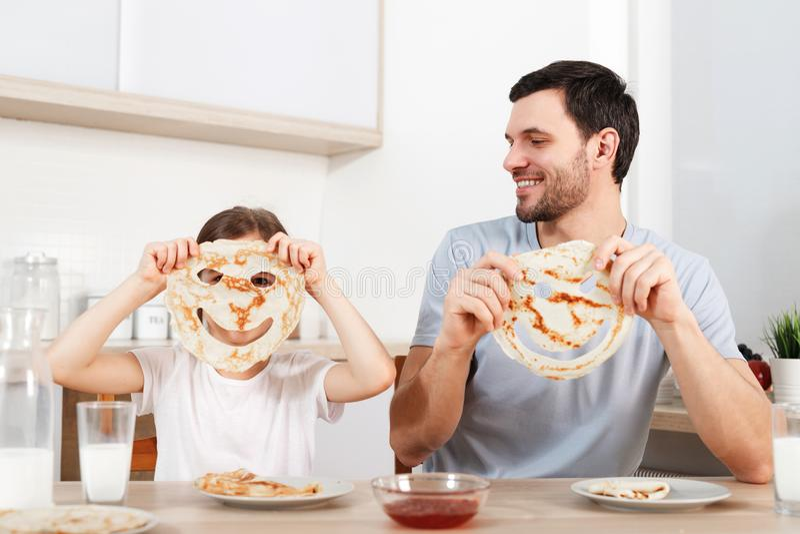 A imagem da menina pequena alegre cobre a cara com a panqueca, senta-se perto de seu pai afetuoso na cozinha, tem a ceia saboroso imagens de stock