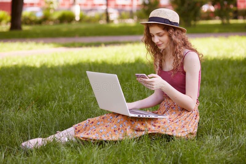A imagem da mulher à moda bonita no chapéu, sentando-se na grama verde com portátil e telefone nas mãos, tem as classes em linha, foto de stock royalty free