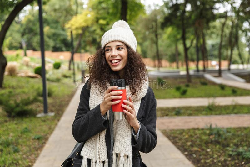 Imagem da mulher atrativa 20s na roupa morna, guardando o copo da garrafa térmica ao andar através do parque verde fotos de stock