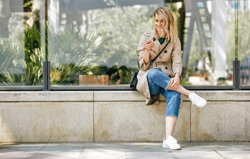 Imagem da mulher bonita nova que escreve mensagens no telefone celular, assento exterior na rua da cidade no dia ensolarado imagem de stock royalty free