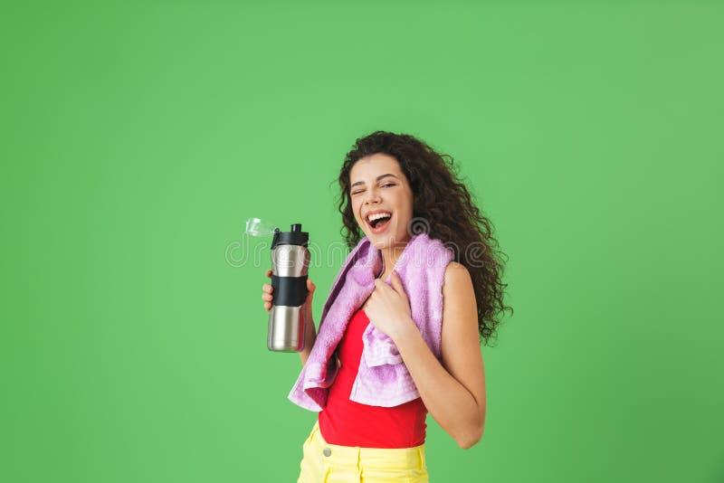 Imagem da mulher caucasiano 20s no júbilo do sportswear e da água potável após a formação fotografia de stock royalty free