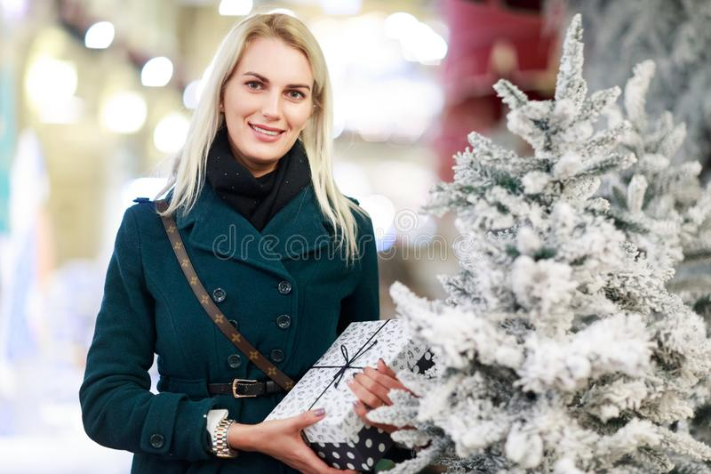 Imagem da mulher com o presente na caixa da árvore do White Christmas na loja fotografia de stock royalty free