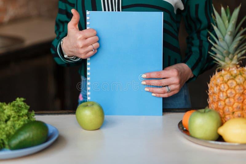 Imagem da mulher com os frutos e o caderno que mostram os polegares acima Tiro próximo nenhuma cara imagem de stock