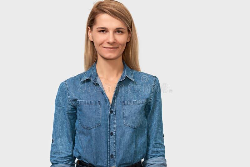 Imagem da mulher de negócio de sorriso bonita com o cabelo louro que está na camisa azul da sarja de Nimes sobre o fundo branco foto de stock royalty free