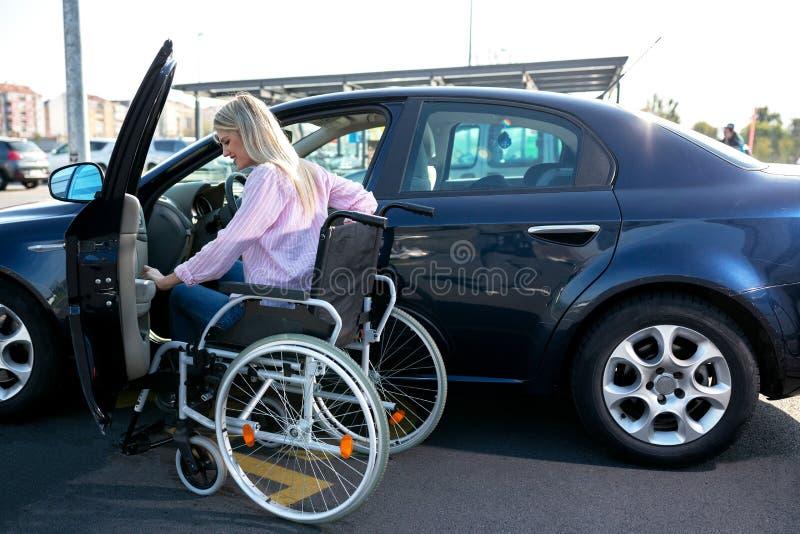 Imagem da mulher deficiente nova que tenta alcançar seu carro imagens de stock