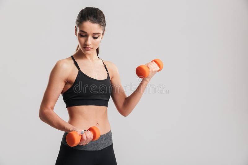 Imagem da mulher desportiva magro que faz exercícios com dumbbe vermelho pequeno fotografia de stock