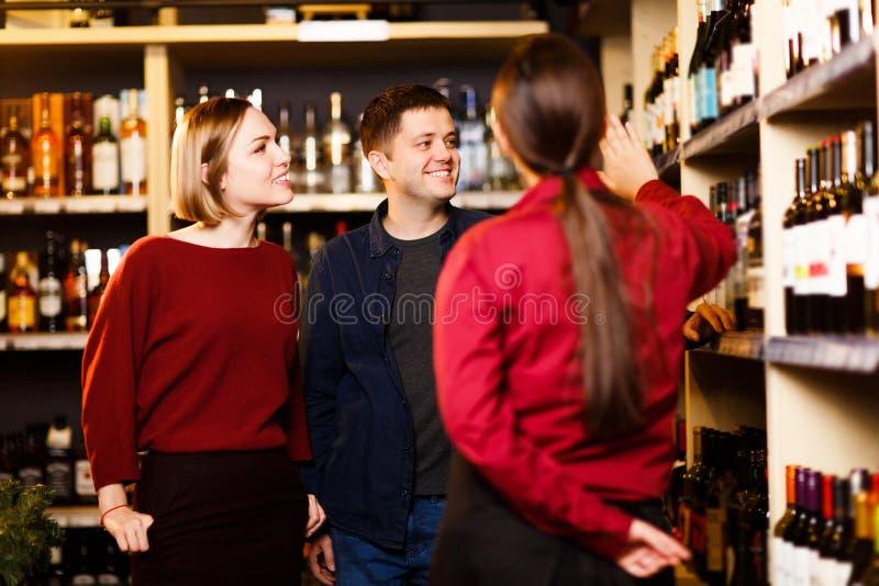 Imagem da mulher, do homem e do vendedor da parte traseira na loja com vinho imagem de stock royalty free