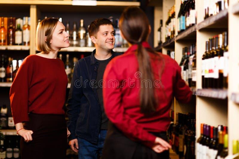 Imagem da mulher, do homem e do vendedor da parte traseira na loja com vinho foto de stock