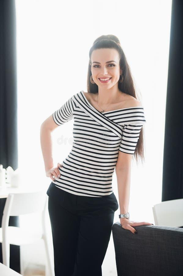 A imagem da mulher feliz nova vestiu-se na blusa que está no café ao olhar a câmera imagem de stock royalty free