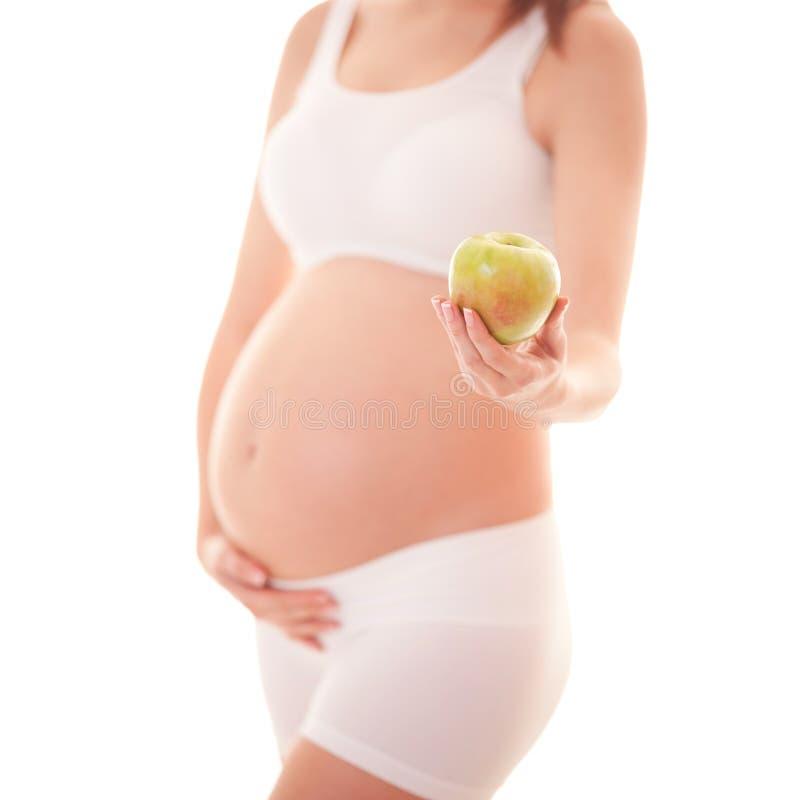 Imagem da mulher gravida que toca em sua barriga grande e que guarda a maçã na mão isolada no fundo branco Fim acima Bonito fotografia de stock