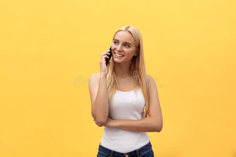 Imagem da mulher lindo em ocasional que está sendo surpreendida ou excitada receber a conversa agradável em seu telefone celular, foto de stock royalty free