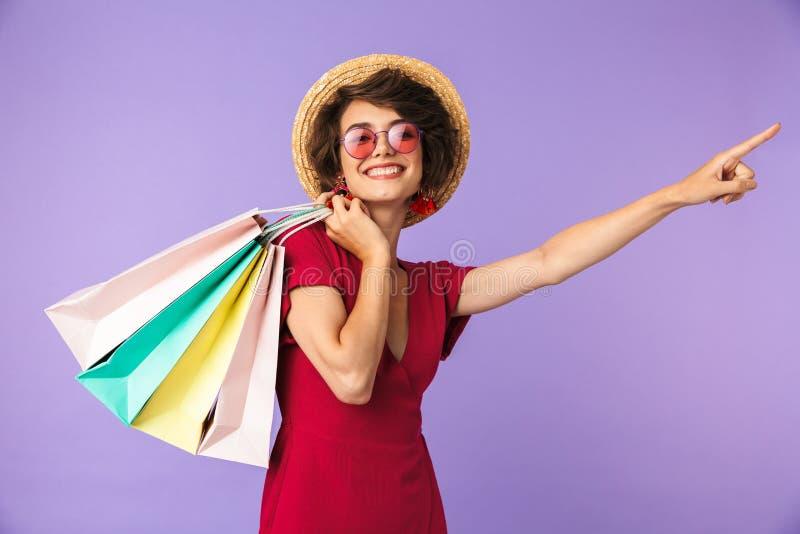 Imagem da mulher moreno entusiasmado 20s no chapéu de palha que guarda o colorfu foto de stock royalty free