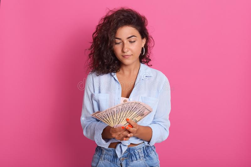 Imagem da mulher moreno nova thounghtful que vestem o tiro azul e das calças de brim que estão sobre o fundo cor-de-rosa do estúd fotografia de stock