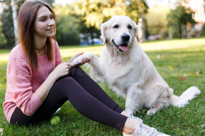Imagem da mulher na caminhada com o Labrador que dá a pata imagem de stock