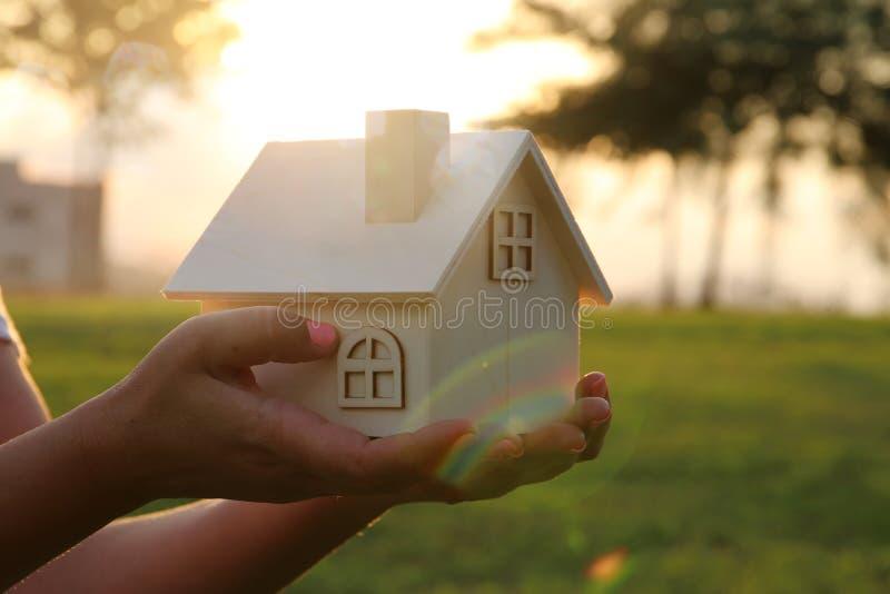 Imagem da mulher que guarda a casa de madeira pequena fora na luz do por do sol fotos de stock