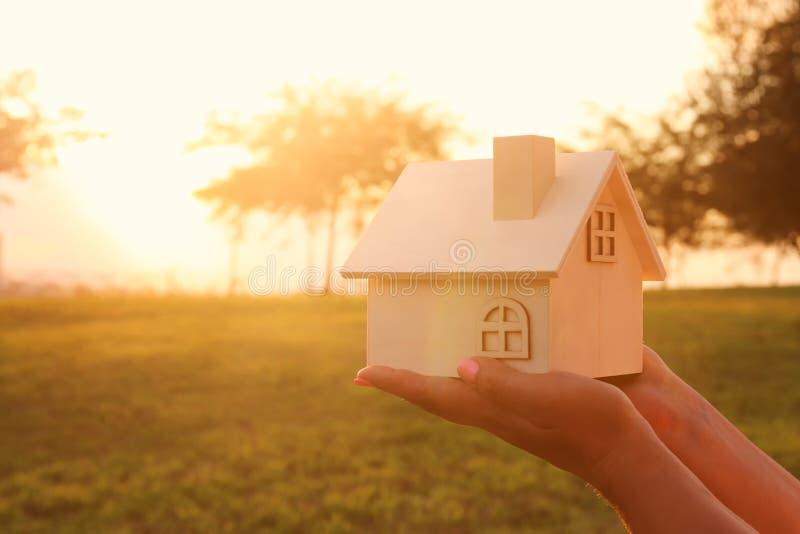 Imagem da mulher que guarda a casa de madeira pequena fora na luz do por do sol imagens de stock