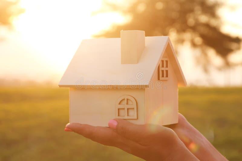 Imagem da mulher que guarda a casa de madeira pequena fora na luz do por do sol foto de stock