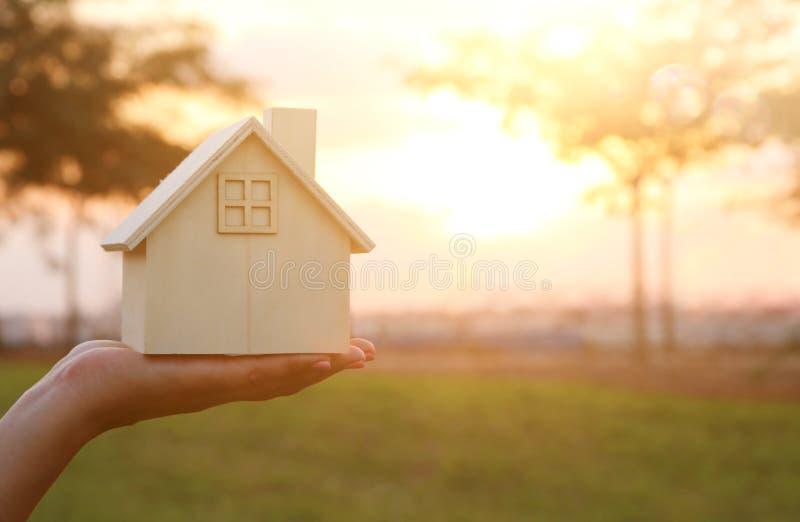 Imagem da mulher que guarda a casa de madeira pequena fora na luz do por do sol imagem de stock royalty free