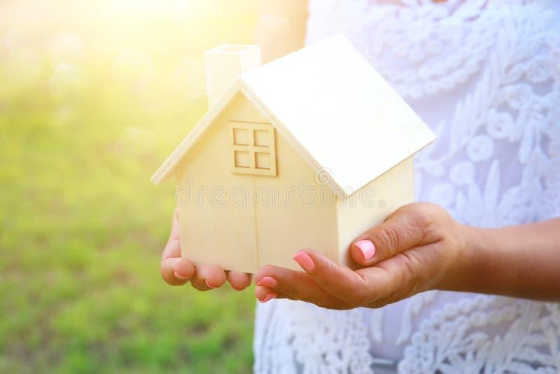 Imagem da mulher que guarda a casa de madeira pequena fora no lig do por do sol imagem de stock royalty free