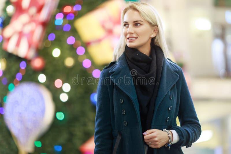 Imagem da mulher que olha ao lado no revestimento no fundo da árvore de Natal na loja imagens de stock royalty free