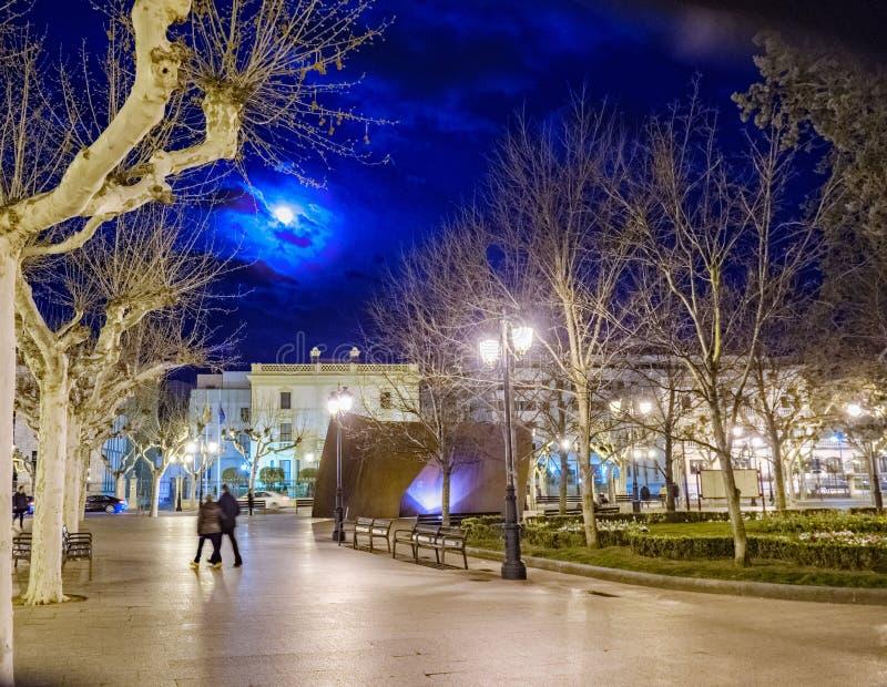 Imagem da noite de uma plaza central do logrono com a Lua cheia coberta parcialmente pelas nuvens, iluminadas muito perto imagens de stock