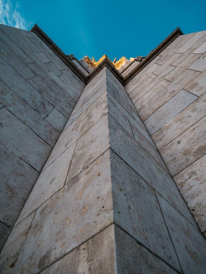 Imagem da parte inferior acima da vista ao longo de uma parede de uma torre com parte superior dourada imagem de stock royalty free