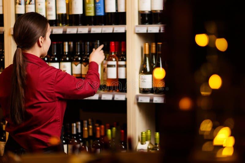 Imagem da parte traseira da jovem mulher na loja de vinho imagem de stock